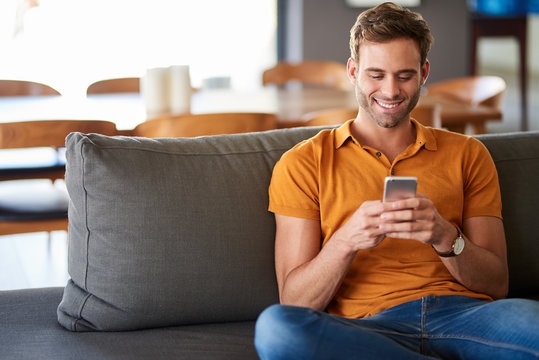 Young man texting on his living room sofa and smiling