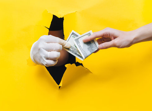 Hand of a woman patient gives money in the form of hundred-dollar bills to the doctor in a white medical glove. Yellow paper background, torn hole. The concept of payment for treatment. Gynecology.
