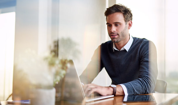 Young businessman using a laptop while working from home