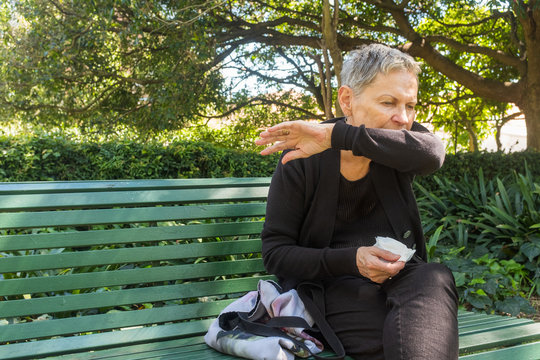 Elderly woman sitting on park bench outdoors coughing into elbow and holding tissue - coronavirus concept (selective focus)