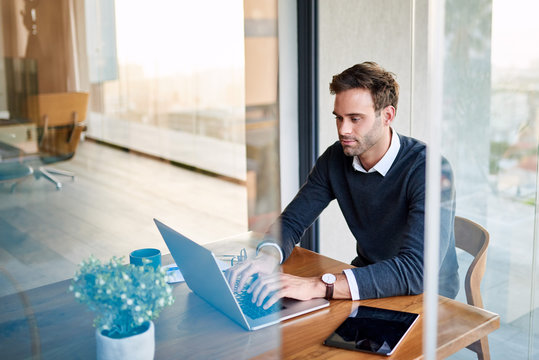 Young businessman at work on a laptop at home