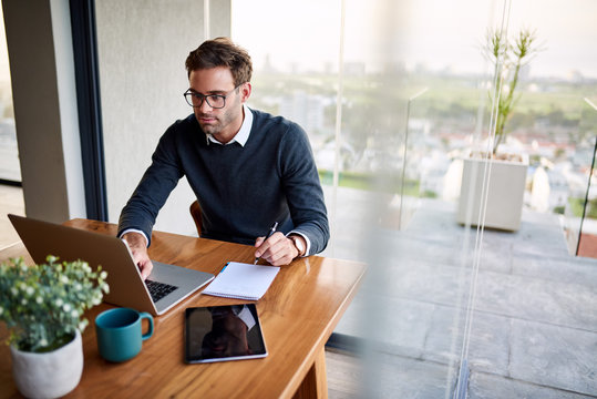 Businessman writing notes while working from home on a laptop
