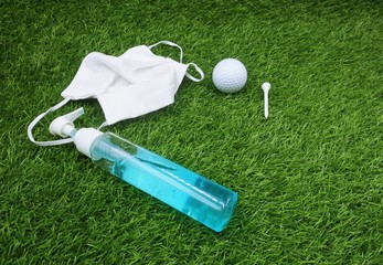 Golfer is preparing hand gel face mask golf ball and tee before go to play golf to prevent corona virus