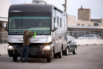 "A man cleans the window of his recreational vehicle as ""snowbirds"" and other Canadians return to Canada in Lacolle"