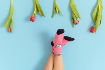 children's legs in funny socks raised up on a blue background, feet having fun, creative concept