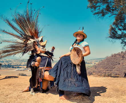 Mexican dancers posing at camera with tufts and pre-Hispanic dress