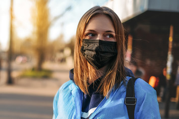 Coronavirus in Europe. the girl is standing by the road in a protective medical mask.