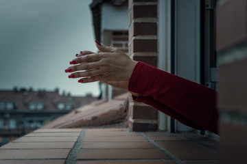 a woman's hands with red nails sticking out the window to clap. coronavirus quarantine