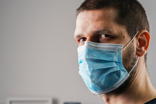 Close up Portrait of caucasian man adult wearing anti-virus bacteria pollution protective mask at home or work head shot side view disease threatened