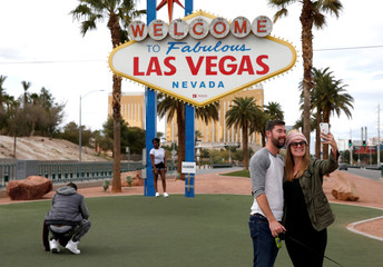 """Sean Hemmer and Emily Marks of San Luis Obispo take a selfie at the normally crowded """"Welcome to Las Vegas"""" sign"""