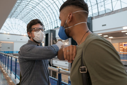 Travelers shake hands with their elbows to prevent disease transmission.