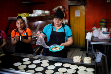 A woman prepares traditional food for takeout in a family-owned restaurant after El Salvador's government announced the closing of restaurants and measures to alleviate the effect of the coronavirus disease (COVID-19), in Antiguo Cuscatlan