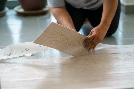 A person installing new vinyl tile floor, a DIY home project.