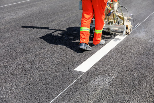 Road workers use hot-melt scribing machines to painting dividing line on asphalt road surface in the city.