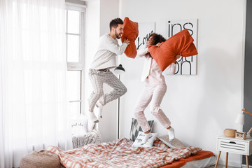 Happy young couple fighting on pillows in bedroom