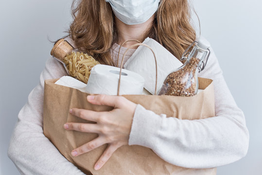Consumer buying panic about coronavirus covid-19 concept. People buying essentials in bulk at supermarkets concept. Woman hold shopping bag with rolls of toilet paper, pasta and buckweat