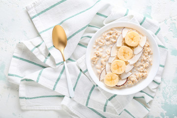 Bowl with tasty sweet oatmeal on color background