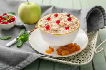 Bowl with tasty sweet oatmeal on tray
