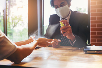 Businessman with mask applying alcohol spray for cleaning and protecting colleague hands from virus...