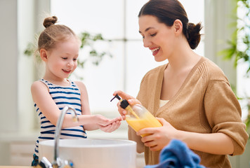 girl and her mother are washing hands