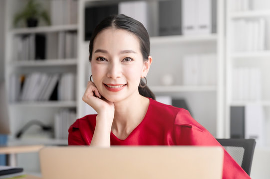 Beautiful asian woman working on a laptop at work. She looked straight at the camera and showed confidence.