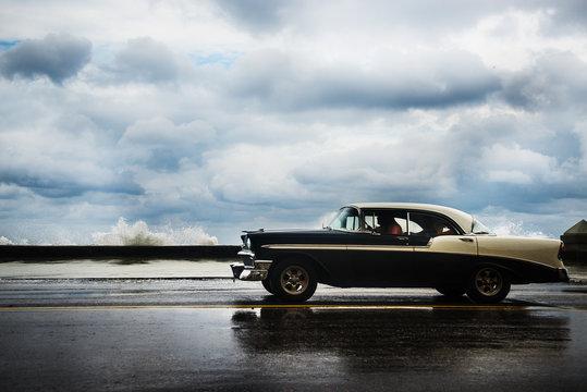 1950's car driving along the Malecon on a cloudy day, Havana, Cuba