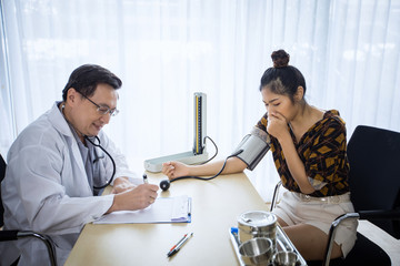 Doctor meeting and explaining medication to woman patient in his office at Hospitals