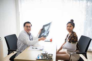 The doctor is explaining about the brain X-ray results to a female patient in his office at Hospitals