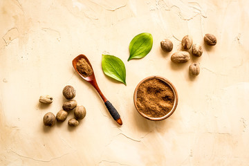 Nutmeg - ground indian condiment in spoon - on beige background top-down