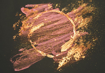 Glitter on abstract golden and pink watercolor stains, shiny round frame on black background