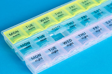 Organizer for medical pills on a blue isolated background close-up. Organization of taking pills of the day.