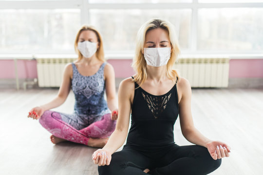 Two girls in medical masks do yoga in a closed Studio in sports clothes. Quiet meditation in the face of a virus epidemic. Group meditation