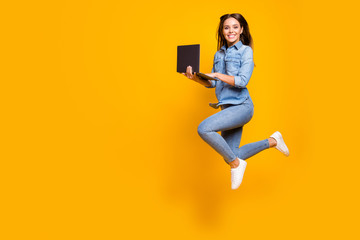 Full length profile photo of funny business lady jump high up hold notebook hands addicted worker always online wear casual denim outfit white sneakers isolated yellow color background