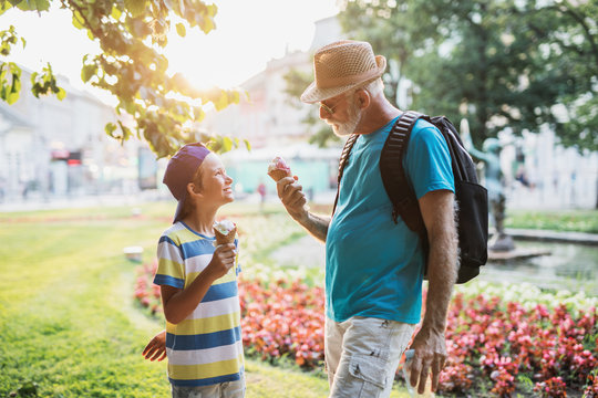 Happy grandfather enjoying with his grandson while eating ice cream outdoors in park.