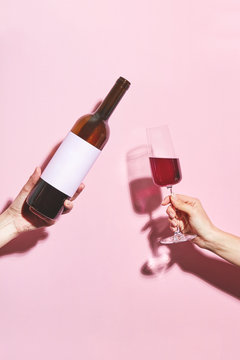 Hands holding a glass of wine and a bottle on pink background. Glass of  wine in female hand. Party insta time.