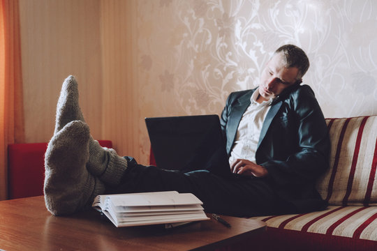 Work From Home online, freelance, remote job in coronavirus crisis, quarantin. Company employee, developer works from home in jacket, comfy pants, knitting socks. WFH comfy outfit. Selective focus.