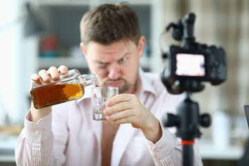 Portrait of man pouring whiskey into glass from bottle. Guy looking drunk and filming on videocamera. Unbutton shirt and bruise under eye. Production on camera