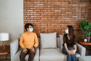 Man and woman wear face masks, sit apart, social distancing