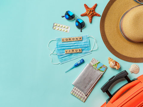 Coronavirus covid-19 and travel concept. Summer vacation and beach rest symbols and breathing mask on blue background. Flat lay or top view. Copy space for text or design.