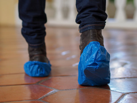 Man with blue shoe covers worn over boots with red shoe laces standing on a tiles, closeup side view.