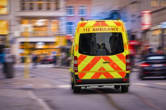 Back view of emergency ambulance car in a blurred street