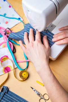 Woman hands using the sewing machine to sew the face mask during the coronavirus pandemia. Domestic sewing due to the shortage of medical materials.