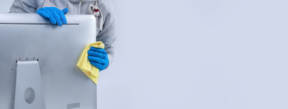 Young woman housekeeper in apron is cleaning silver computer surface with blue gloves, wet yellow rag, close up, copy space, blank design concept.