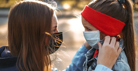 A girl with a child is standing on the road in a protective medical mask. Dangerous virus infection. Coronovirus in Europe