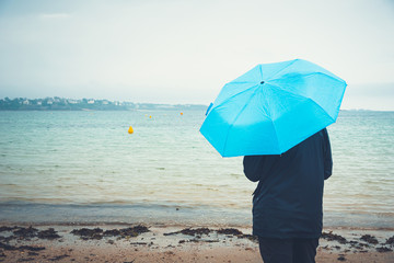 Woman with blue umbrella standing before the sea shore on a mood