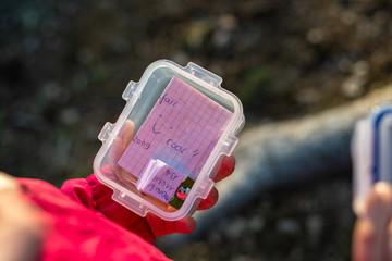 Geocaching Dose in der Hand eines Kindes