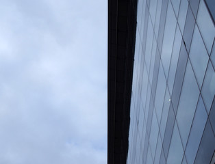 vertical upwards view of a modem office building with a blue cloudy sky on one side reflected in the windows