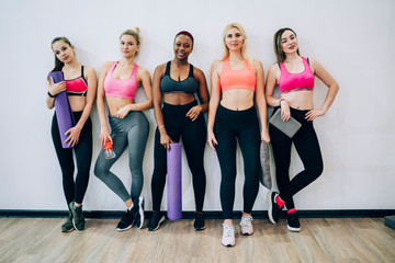 Group of fit women leaning on wall