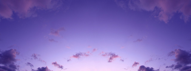 Beautiful background of the evening sky with clouds. Evening clear sky with small fluffy clouds. A banner with a gently purple pink sunset.