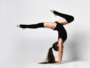 Teenage gymnast in black leotard, knee socks and ballet shoes, performing exercises standing on her hands, upside down, isolated on white. Close-up